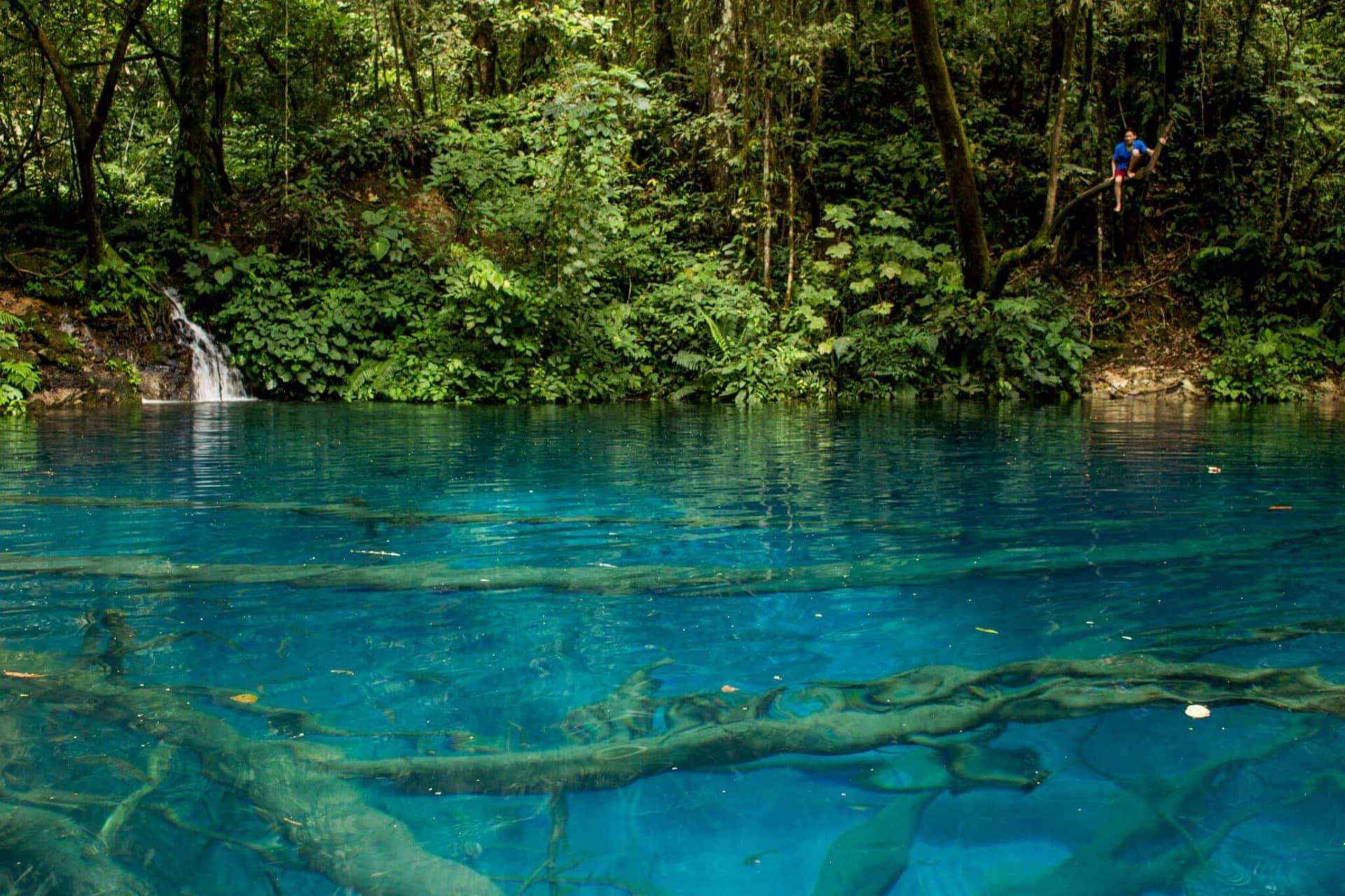 A forest stream flows into the brilliantly blue Lake Kaco in the middle of the rainforest, Danau Kaco, Kerinci Seblat National Park, Sumatra, Indonesia